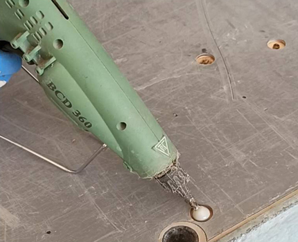 Wypełnianie uszkodzeń sklejki wodoodpornej szalunków budowlanych przed ponownym użyciem.
